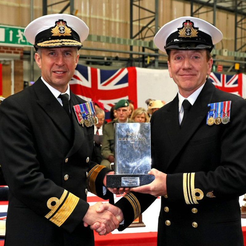 Rear Admiral Keith Blount (left), Assistant Chief of Naval Staff, Royal Navy and Lieutenant Commander Steven Hilson (right), Lynx Simulator Senior Observer, Royal Navy, accept the Breitling Trophy in recognition for delivering exceptional training to Royal Navy Lynx helicopter aircrew.